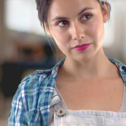 Close up photo of woman looking to the right, wearing a plaid blue shirt and pink lipstick