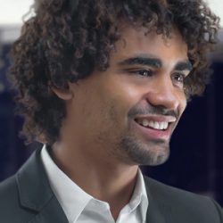 Close up photo of man with curly hair looking to the right and smiling